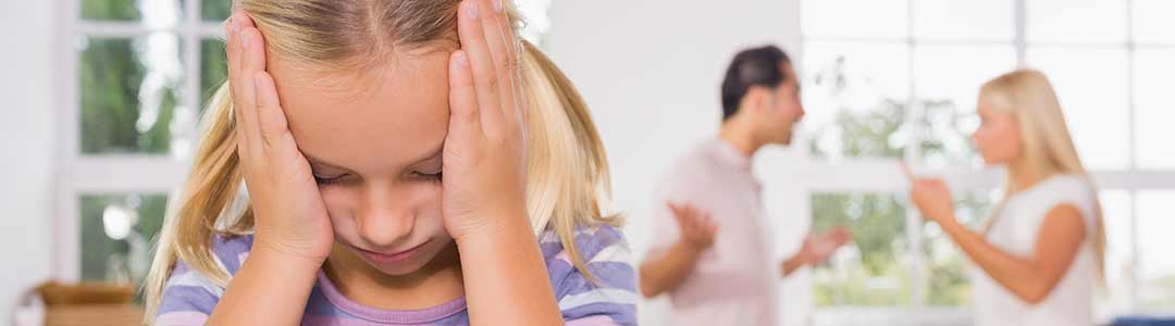 young girl covering ears while parents arguing in background The Webster Law Firm